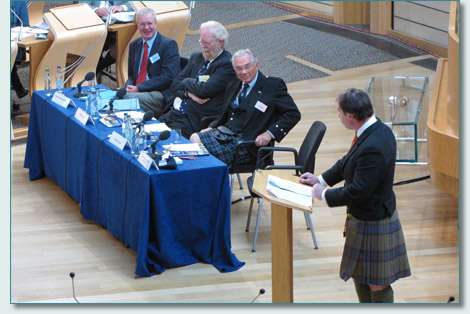 Chief Donald McLaren of McLaren addresses the Clan Convention 2009, with panel Dr. Jim Hunter, David Sellar, Lord Lyon King of Arms, and Bob McWilliam.
